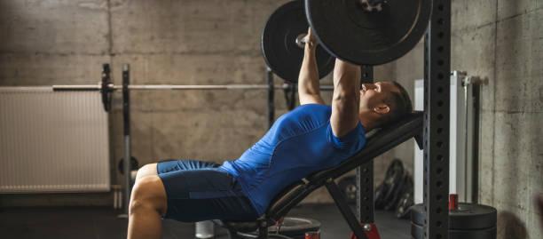 Спортивный мужчина делает жим лежа на наклонной скамье